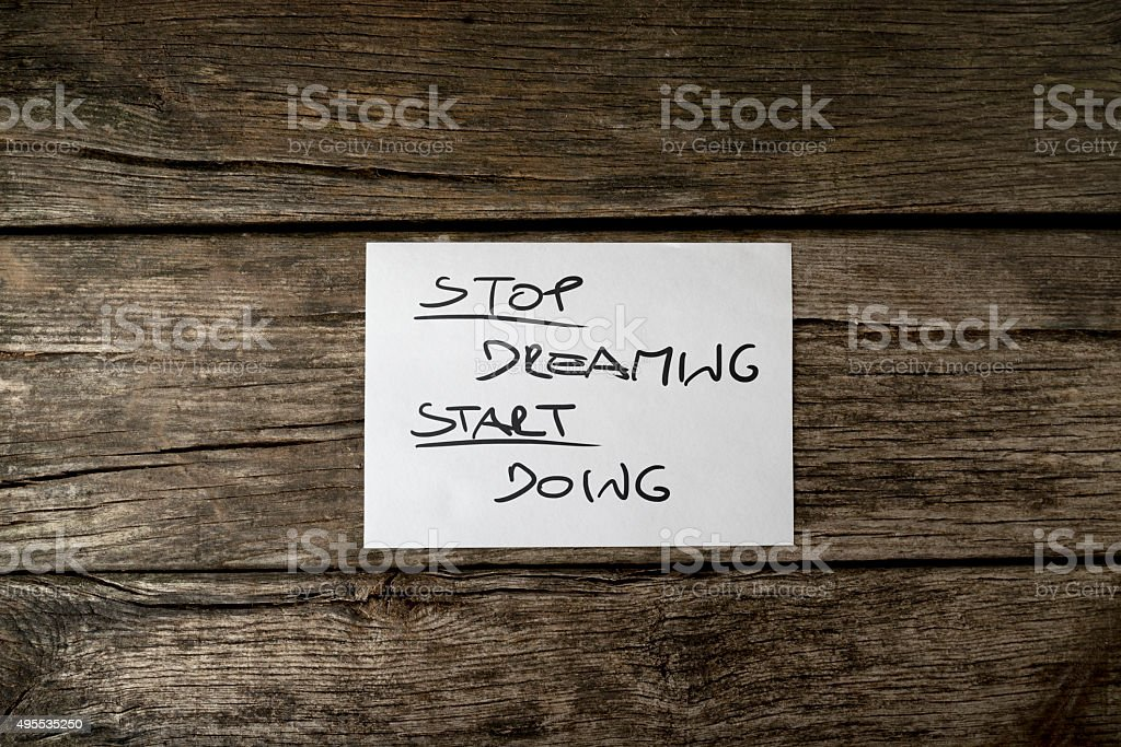 Top view of a Stop dreaming start doing message stock photo