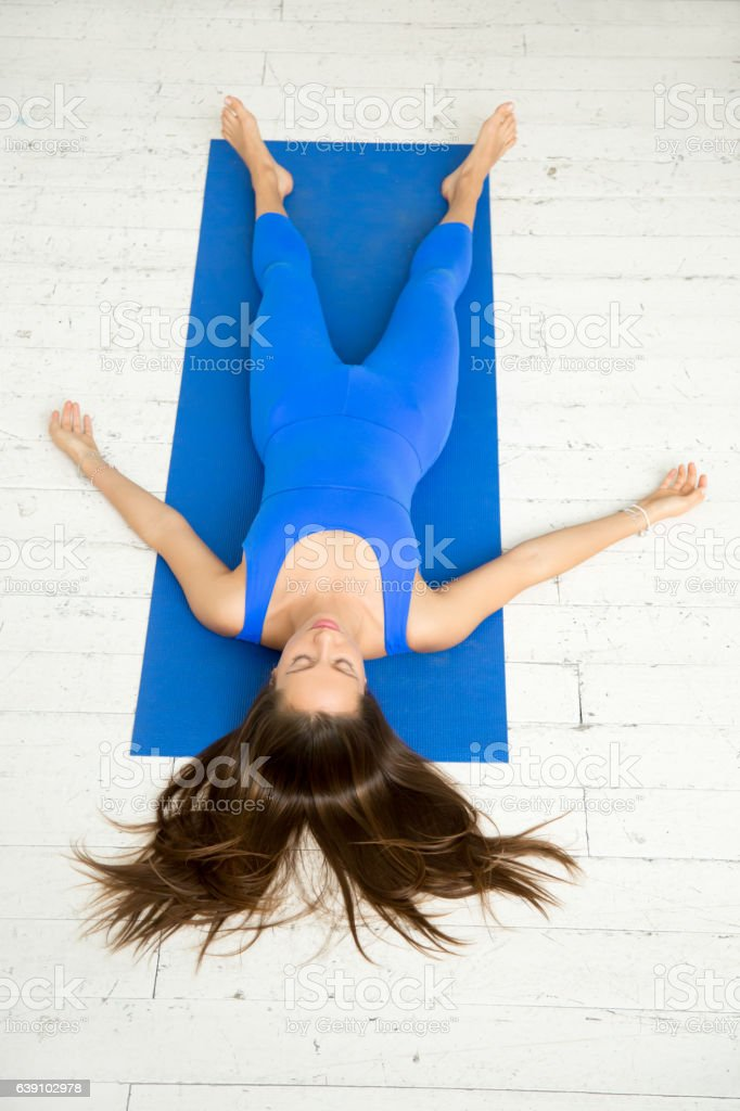Top view of a woman in Corpse pose, white studio stock photo