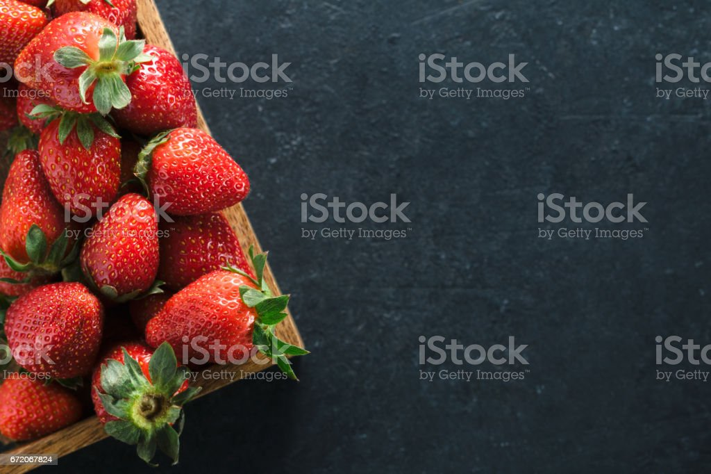 Top view of a wooden box with ripe fresh strawberries on a black table. Place for the text. Healthy food concept. stock photo