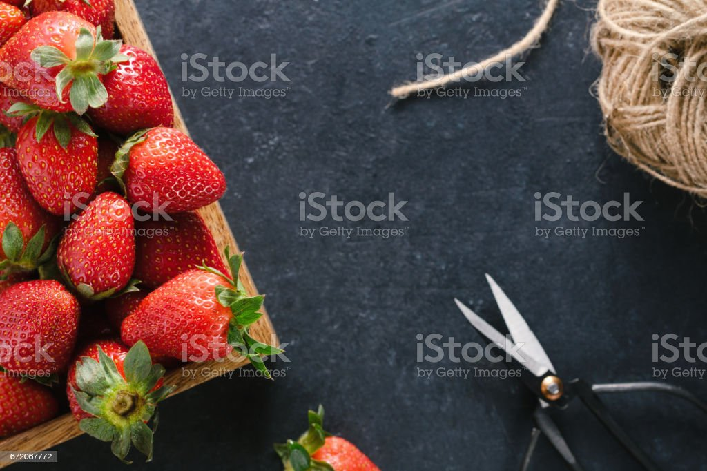 Top view of a wooden box with ripe fresh strawberries, vintage black scissors and twine on a black table. Place for the text. Healthy food concept. stock photo