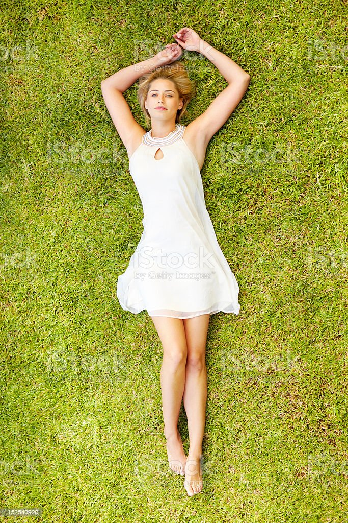 Top view of a young lady lying on grass stock photo