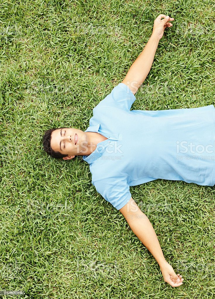 Top view of a young man relaxing on grass stock photo