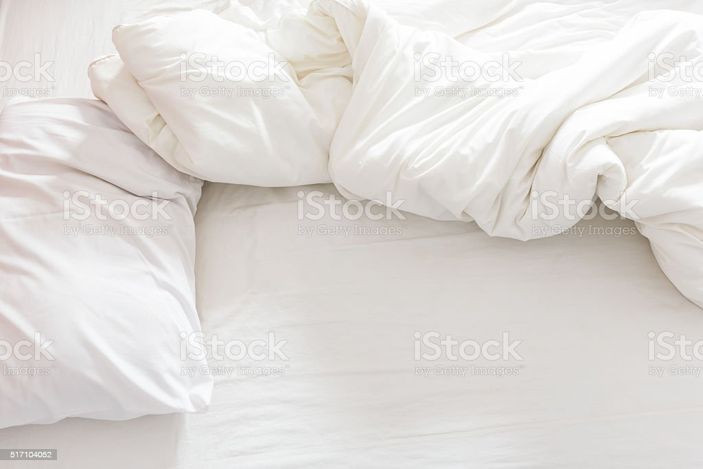 Top view of an unmade bed with a pillow, stock photo
