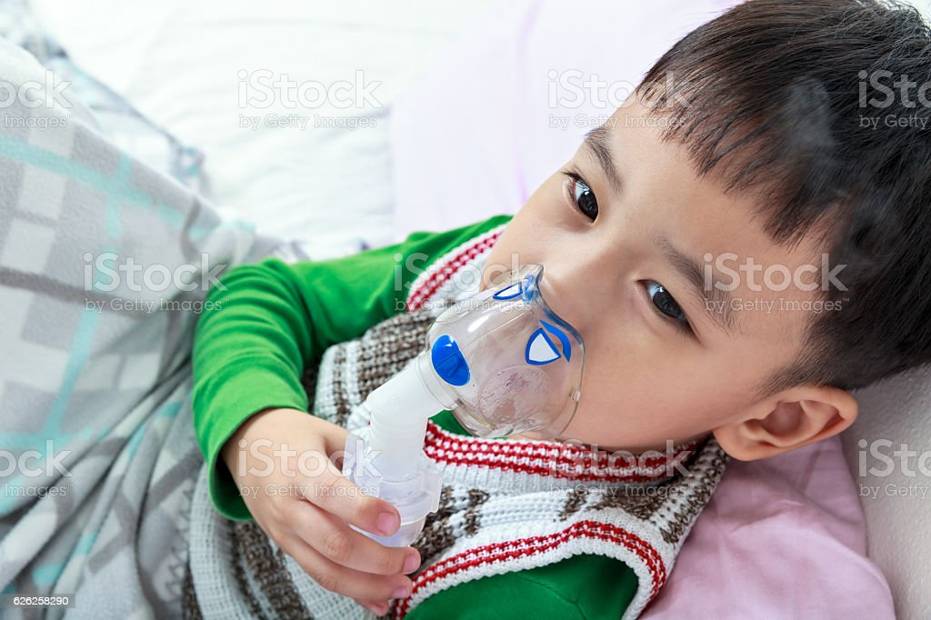 Top view of asian child holds a mask vapor inhaler. stock photo