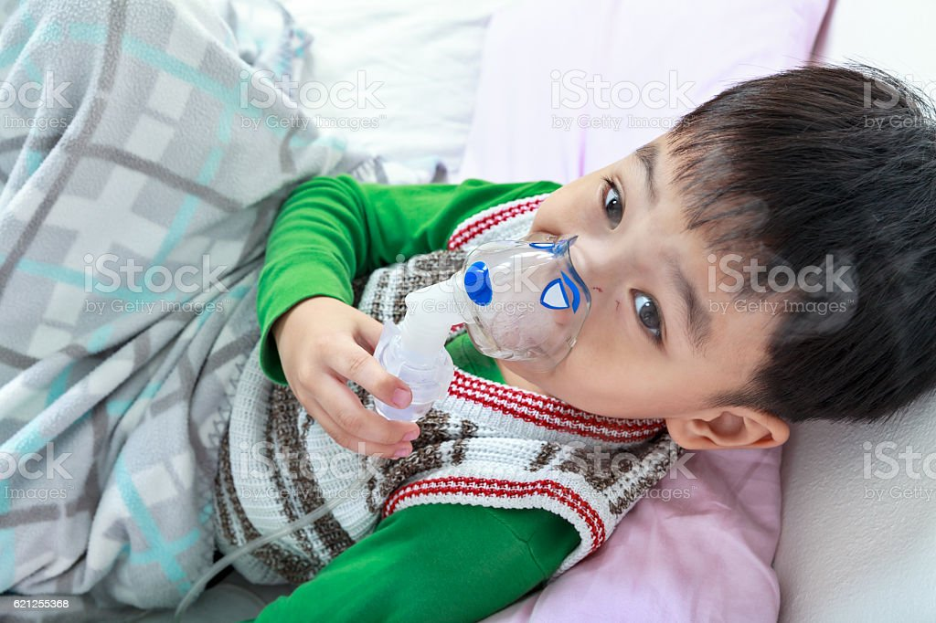 Top view of asian child holds mask vapor inhaler. stock photo