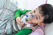 Top view of asian child holds mask vapor inhaler.
