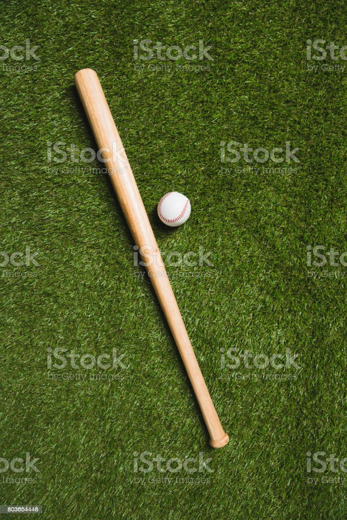top view of baseball bat and ball on grass field stock photo