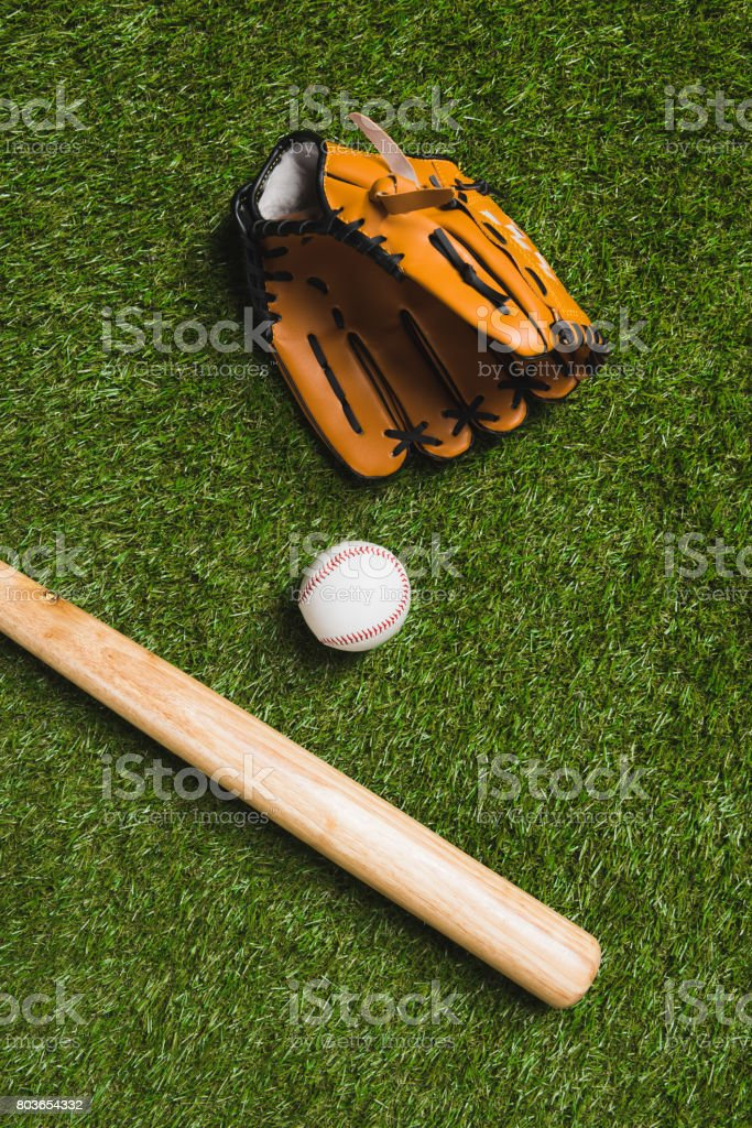 top view of baseball bat with ball and glove on grass stock photo