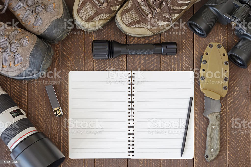 Top view of blank notebook, dirty hiking shoes, Flashlight, Knife stock photo