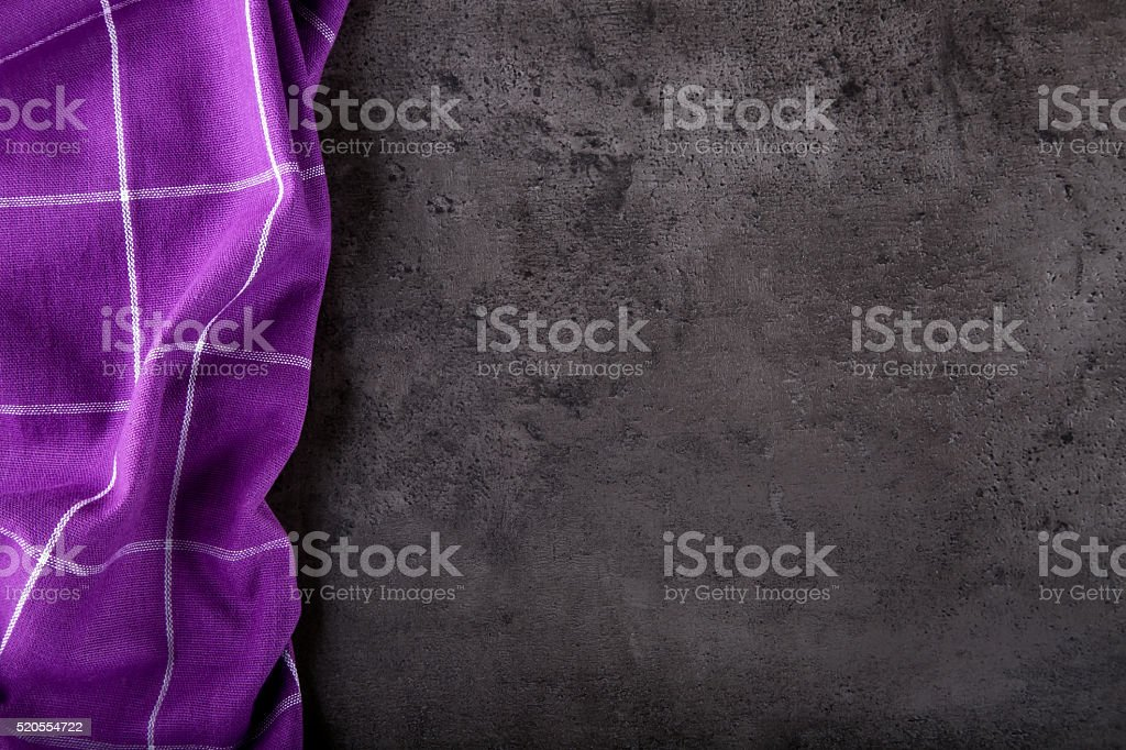 Top view of checkered kitchen purple tablecloth on concrete table stock photo