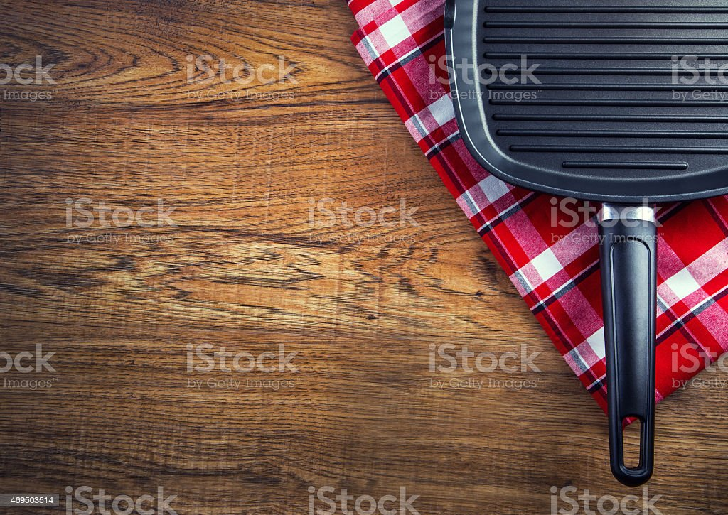 Top view of checkered napkinand teflon pan on wooden table. stock photo