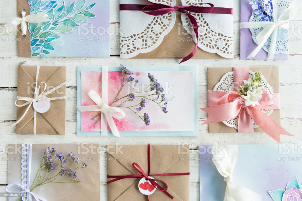 top view of collection of envelopes or invitations on white wooden tabletop, wedding invitation card design concept stock photo