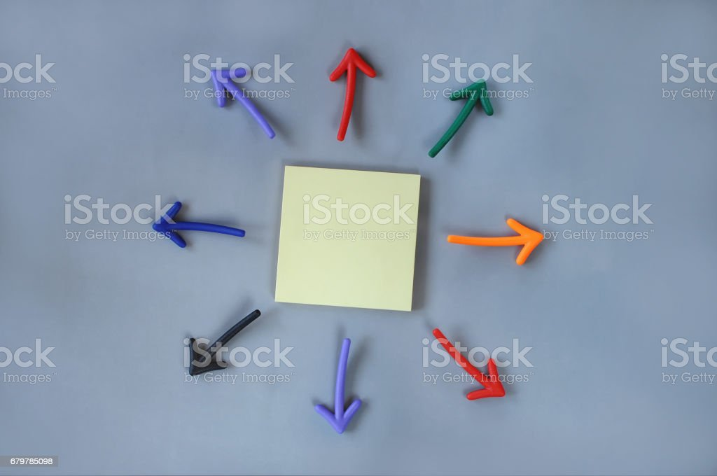 Top view of colorful arrow and yellow sticky note on grey background stock photo