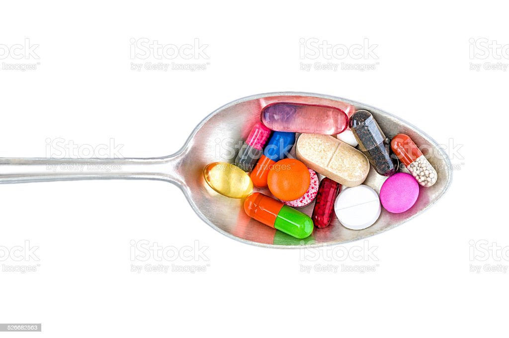 Top view of colorful pills on spoon. White background. stock photo