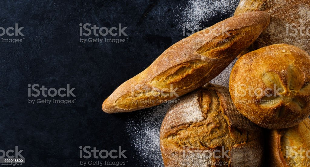 Top view of composition with fresh homemade bread over dark table. stock photo