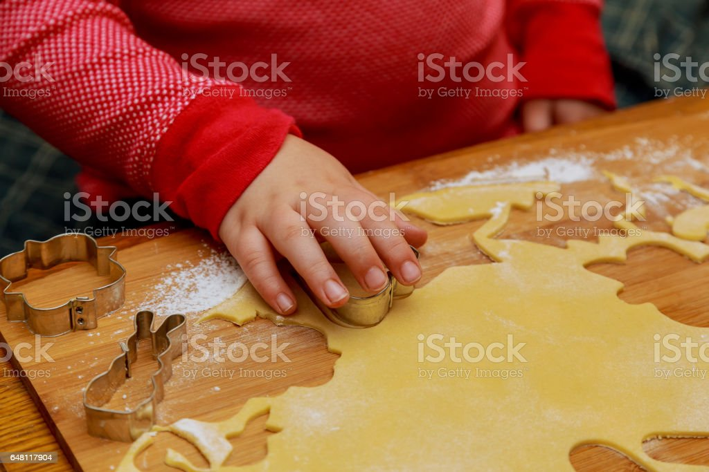 Top view of cutting gingerbread of metal molds by children's hands stock photo