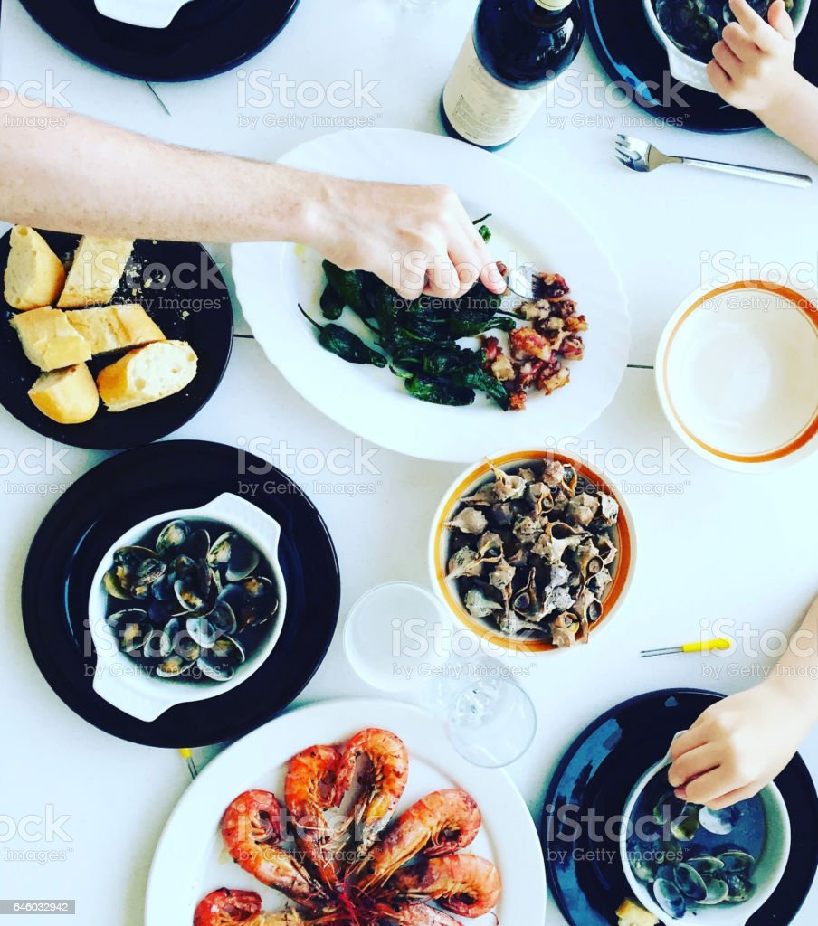 Top view of family eating seafood around a white table from high view angle stock photo