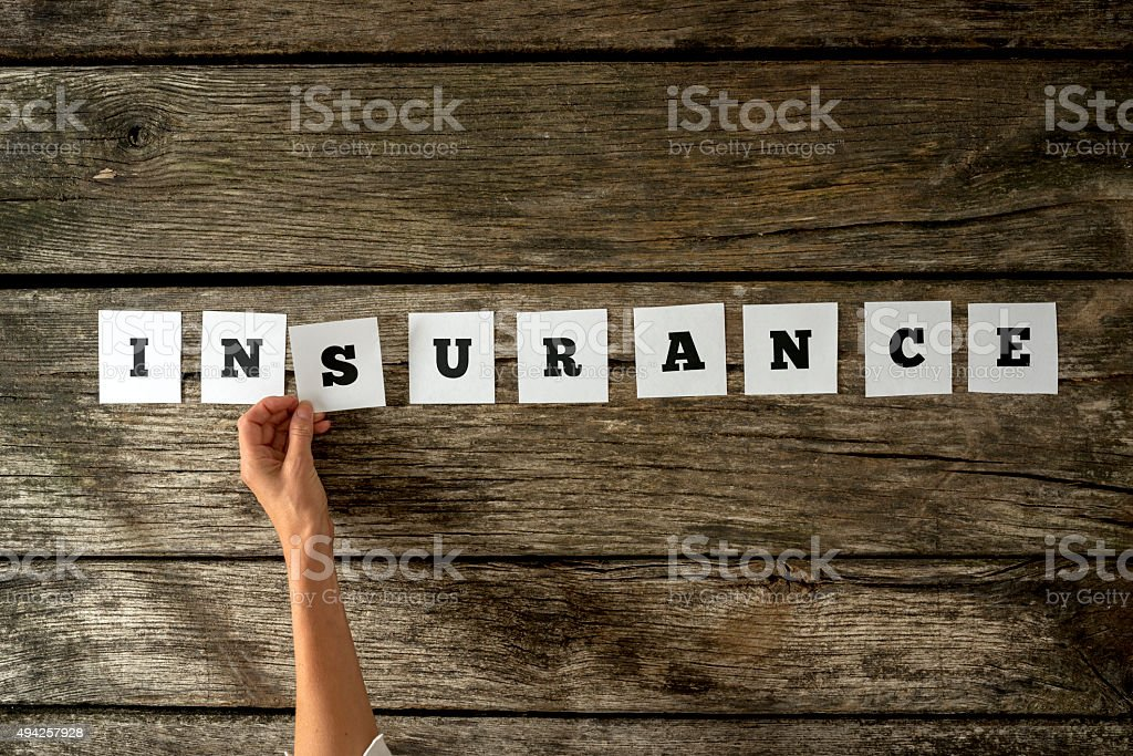 Top view of female insurance agent assembling the word Insurance stock photo