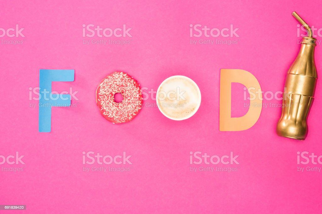 Top view of food word made from donuts and coffee isolated on pink....