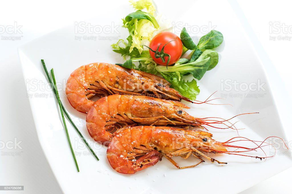 Top view of fresh grilled jumbo prawns with green salad. stock photo