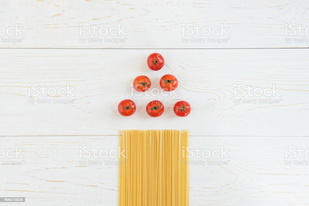 Top view of fresh raw tomatoes and uncooked pasta on wooden table stock photo