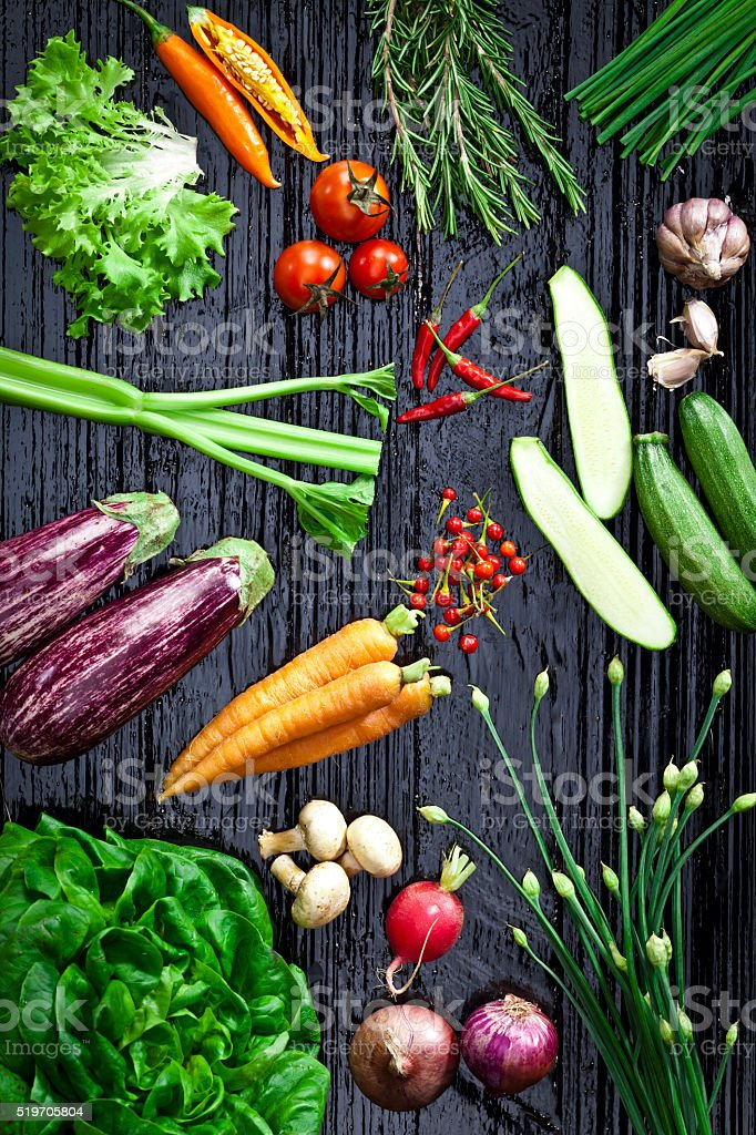 Top view of fresh vegetables and spices on dark background stock photo
