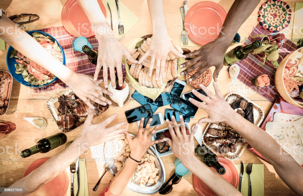 Top view of friend hands with mobile smartphones on food stock photo