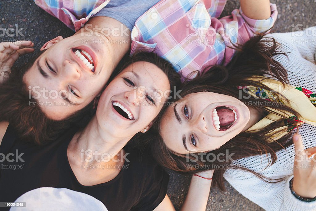 Top view of friends lying down and laughing stock photo