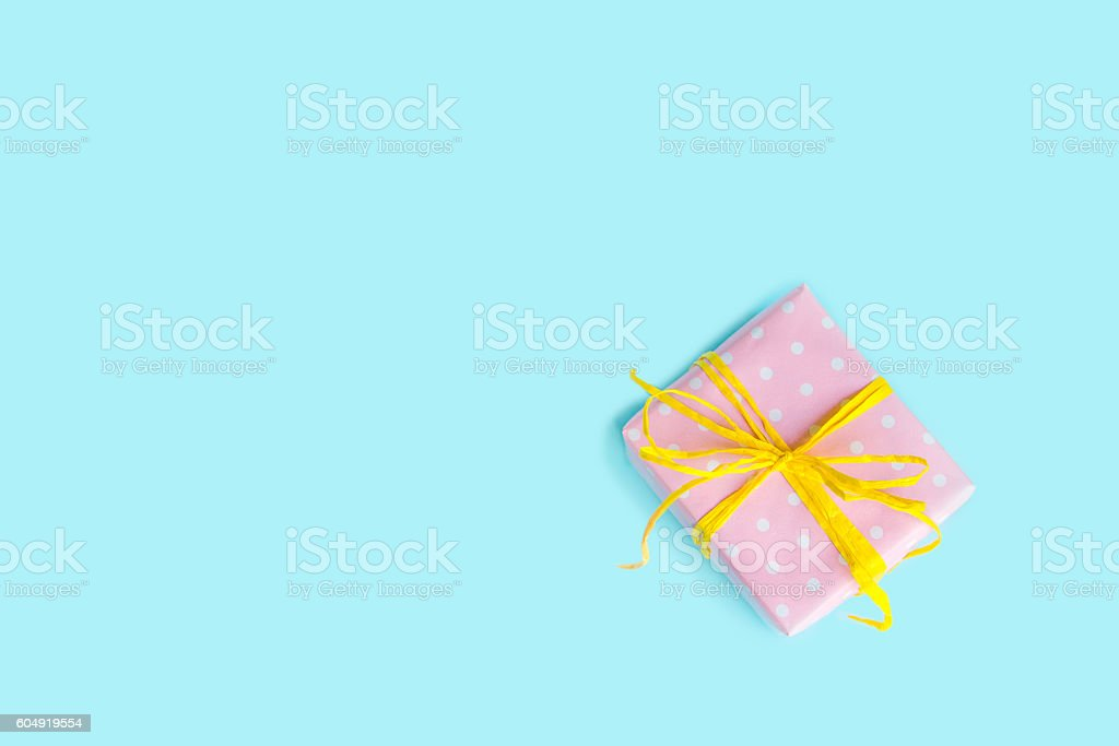 Top view of gift box wrapped in pink dotted paper. stock photo