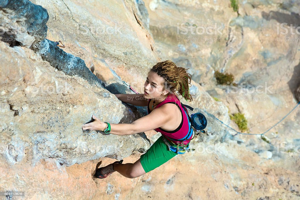Top View of Girl Rock Climber hanging high rocky Wall stock photo