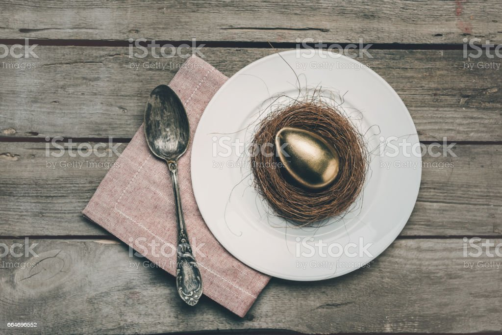 Top view of golden Easter egg in nest on white plate, napkin and vintage spoon on wooden table, Happy Easter concept stock photo