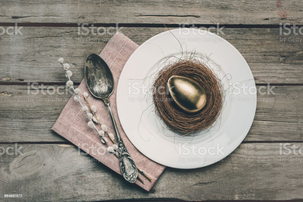 Top view of golden Easter egg in nest on white plate, napkin, catkins and vintage spoon on wooden table, Happy Easter concept stock photo
