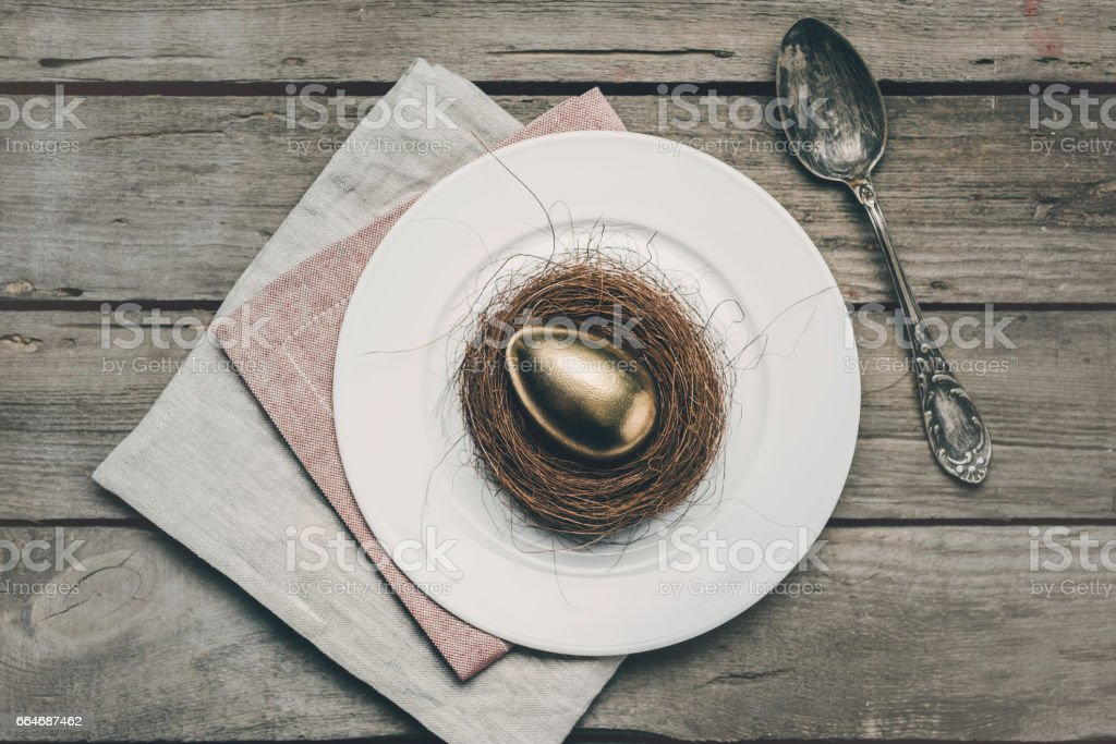 Top view of golden Easter egg in nest on white plate, napkins and vintage spoon on wooden table, Happy Easter concept stock photo