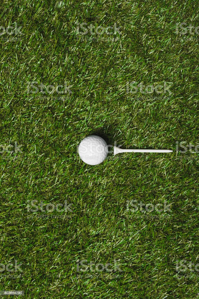 top view of golf ball and tee on grass field stock photo