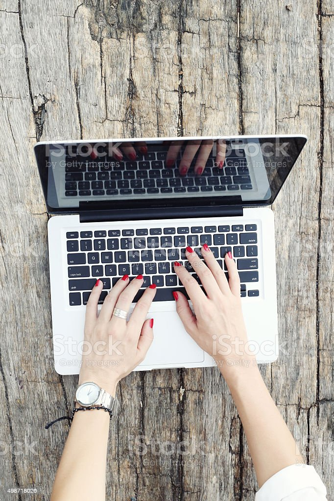 Top view of hand typing on laptop keyboard stock photo