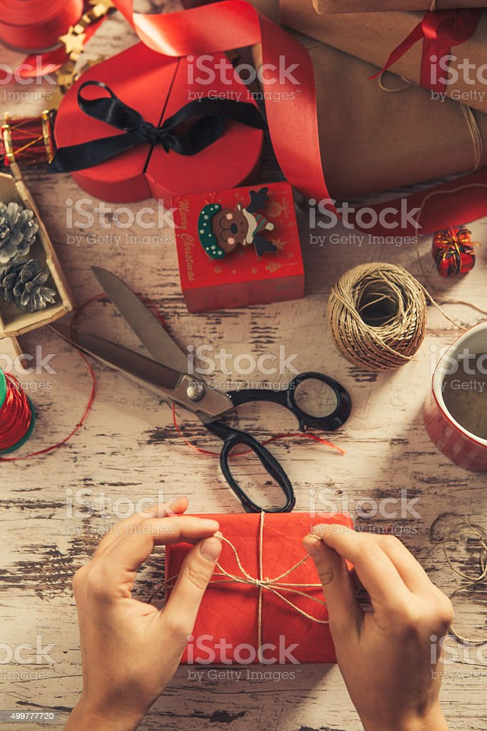 Top view of hands decorating a gift stock photo