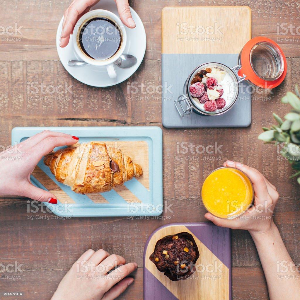 Top view of hands taking food and drink stock photo