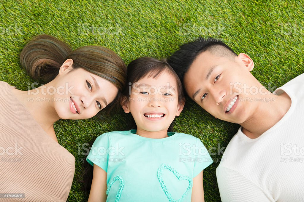 top view of Happy  Young  Family lying on the grass stock photo