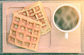 Top view of hot coffee and waffle on wooden coaster.