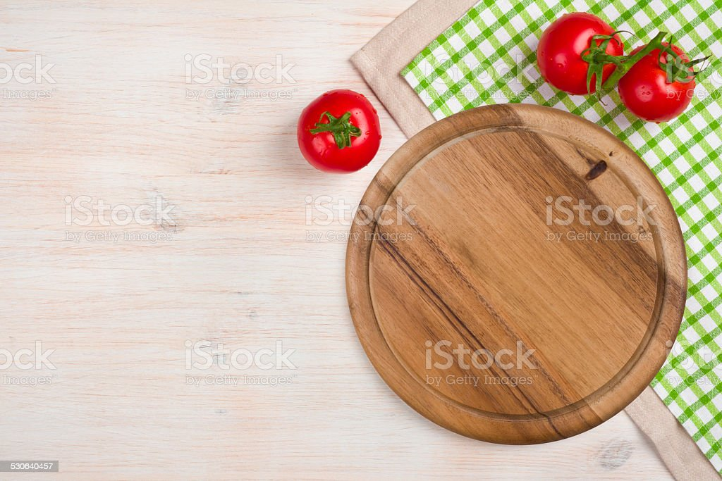 Top view of kitchen cutting board over wooden background stock photo