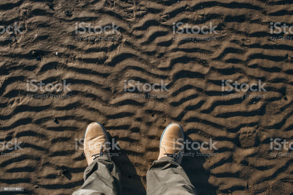Top view of legs and beige suede boots standing on the beach stock photo