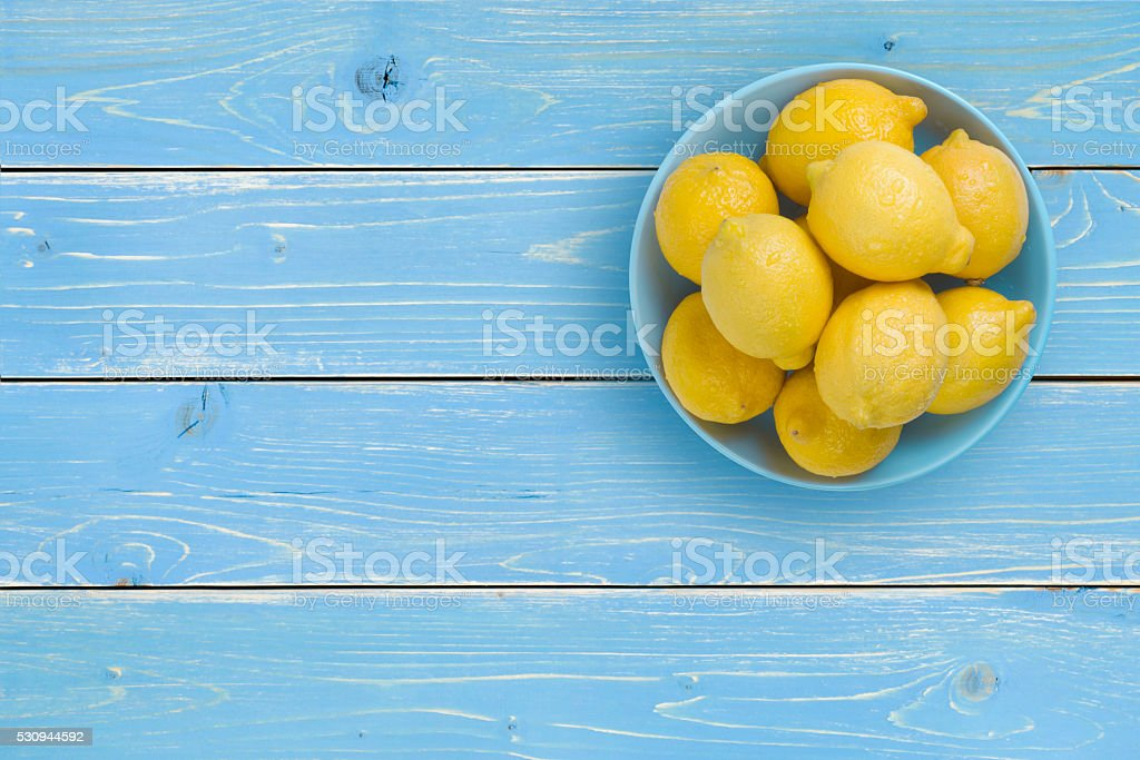 Top view of lemons on blue plate over tropical background stock photo
