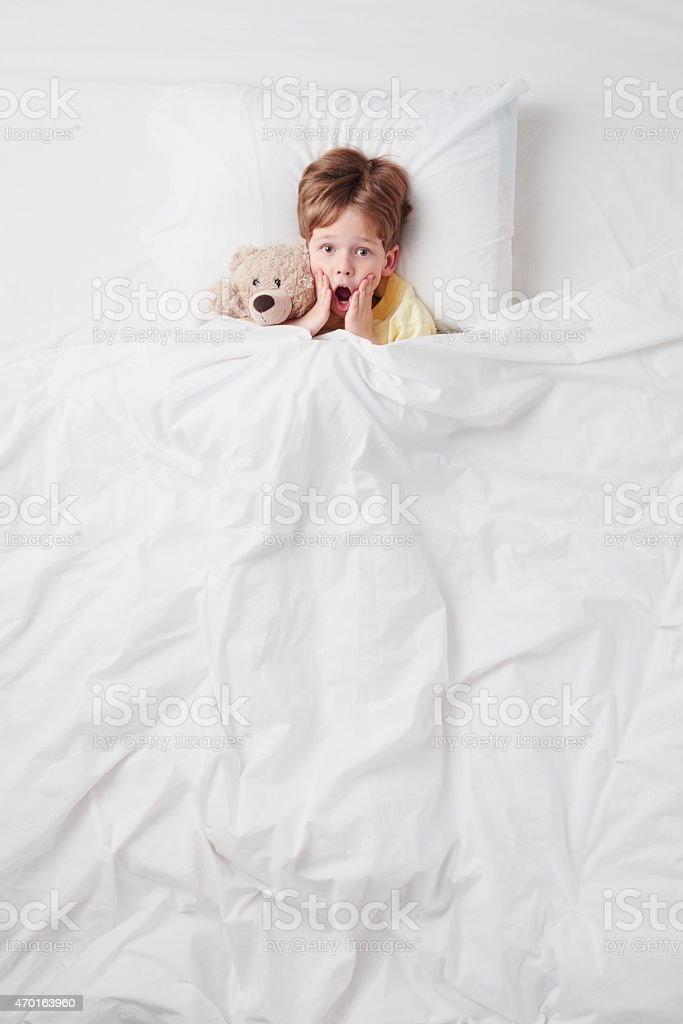 Top view of little scared by nightmares boy under blanket stock photo