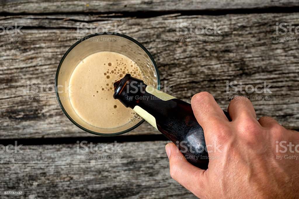 Top view of male hand pouring dark beer in glass stock photo