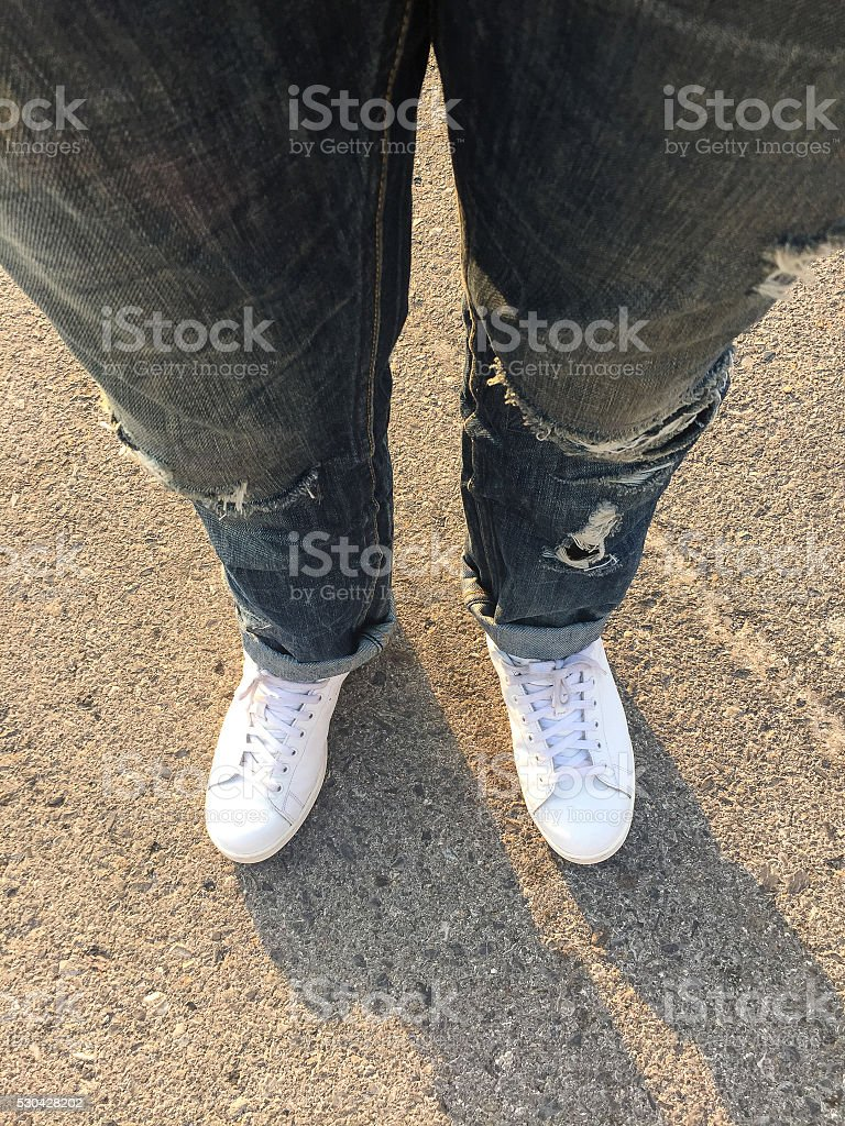 Top view of male wearing ripped jeans and shoes stock photo