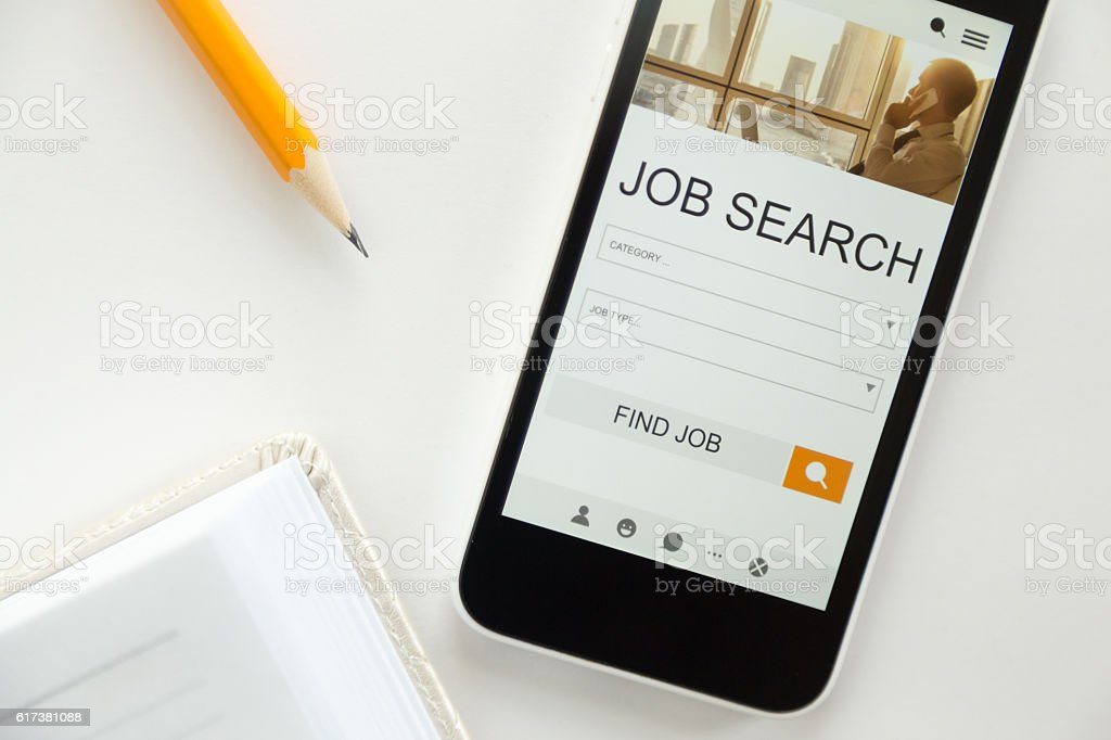 Top view of mobile phone lying on desk, job search stock photo