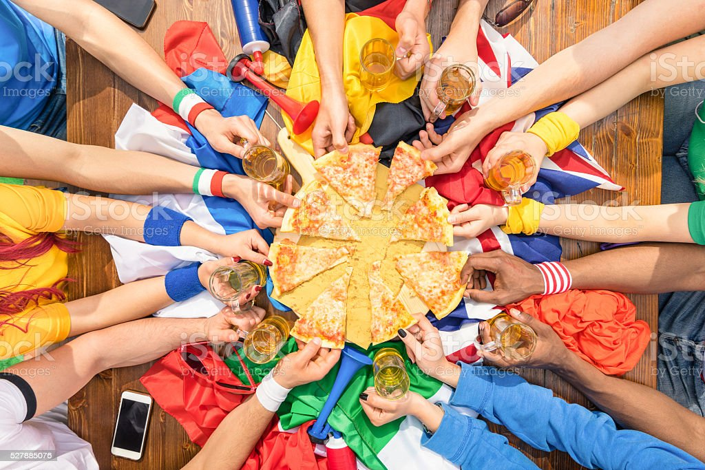 Top view of multiracial hands - Football supporters sharing pizza stock photo
