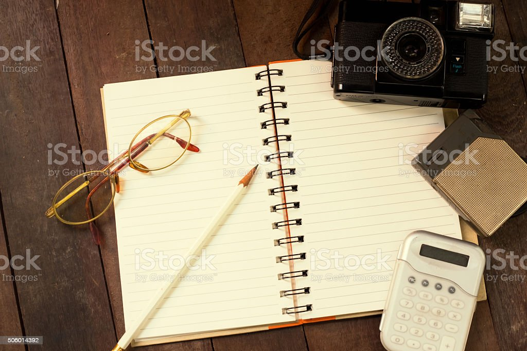 Top view of Notebook, glasses, pencils, calculators, cameras. stock photo