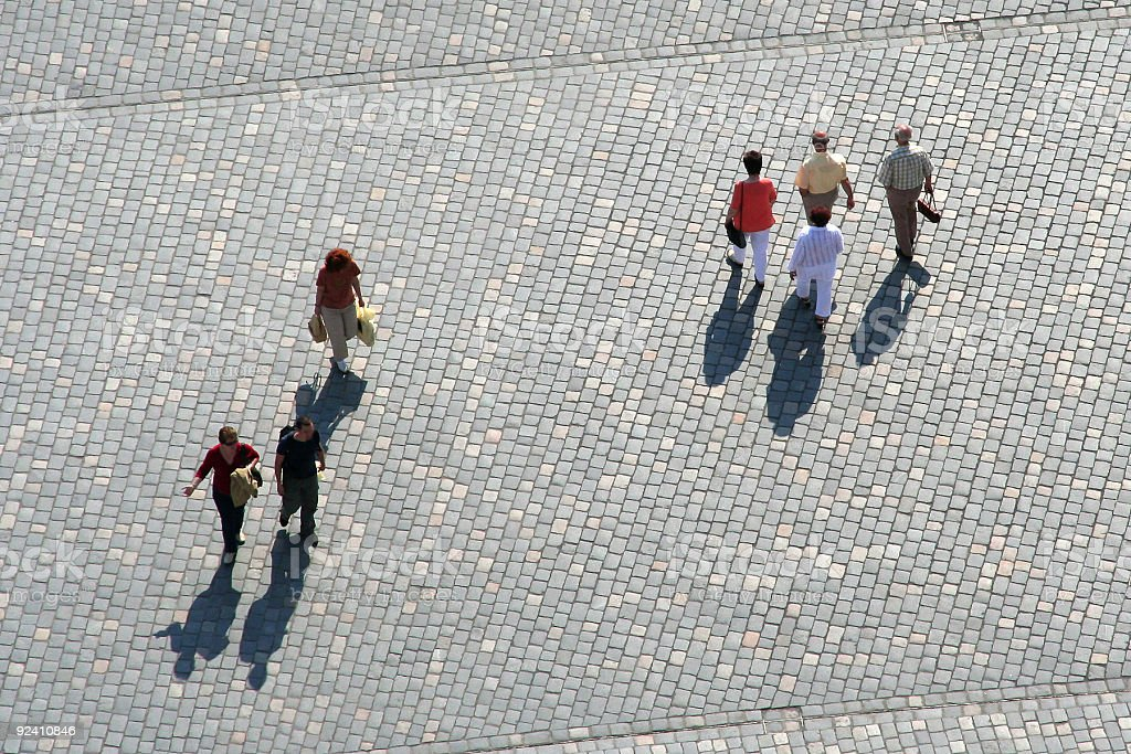 Top view of people walking along square with stone paving stock photo