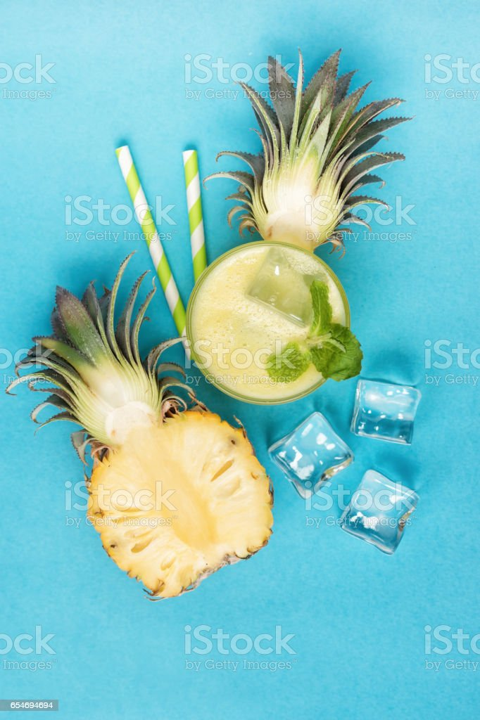 Top view of pineapple half with smoothie and ice cubes stock photo